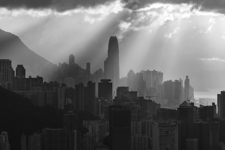 Silhouette of skyline of Hong Kong city with sun ray under sunset