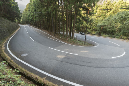Curved winding road in forest in Wakayama, Japan Stock Photo