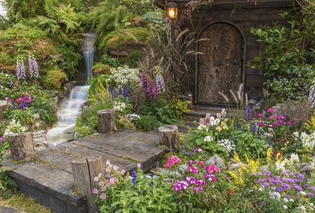Aangelegde achtertuin van oud huis met bloementuin Stockfoto
