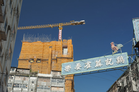 Hong Kong, China - August 9, 2013 : Abandoned residential building, advertising board and construction site in Hong Kong city
