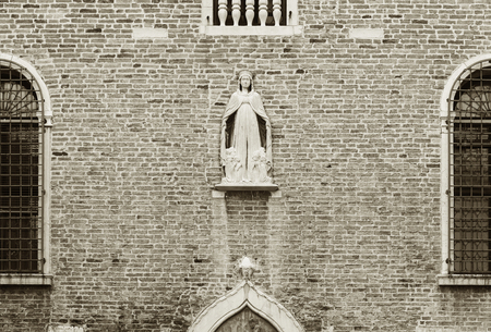 The Virgin Mary statue on wall in Venice, Italy