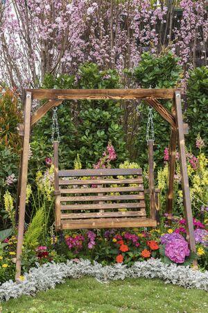 Asiento de columpio de madera en el jardín de flores del patio trasero