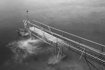 wooden jetty at dusk in black and white