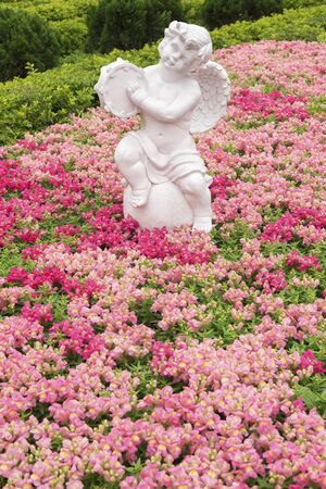 Sculpture of angel in colorful flower garden