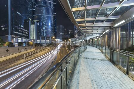 Modern pedestrian walkway and traffic in downtown of Hong Kong city at night
