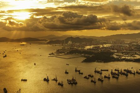 Cargo port and harbor in Hong Kong city under sunset
