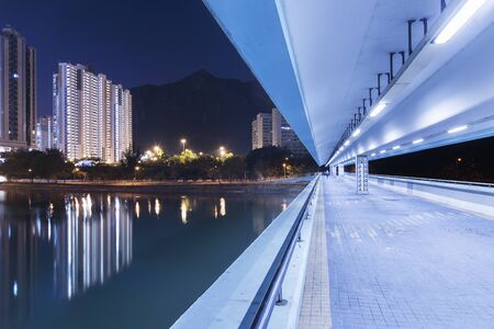 Pedestrian walkway and high rise residential building in Hong Kong city at night Фото со стока