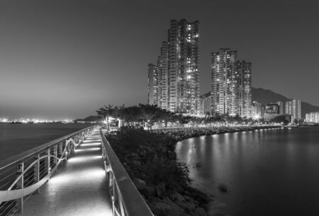 Seaside promenade and high rise residential building in Hong Kong city at night Фото со стока