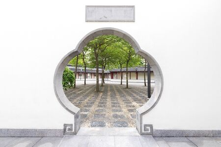 Scenery of Chinese garden with round gate hole Фото со стока