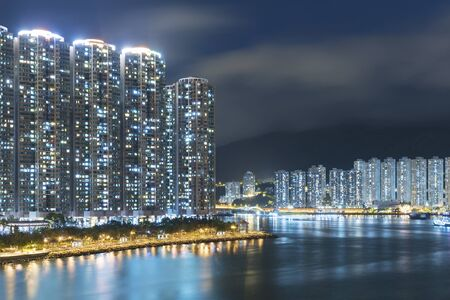 High rise residential building and harbor in Hong Kong city at night