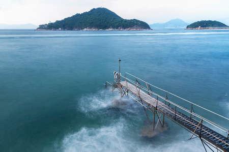 Idyllic landscape of jetty and island in Hong Kong Фото со стока