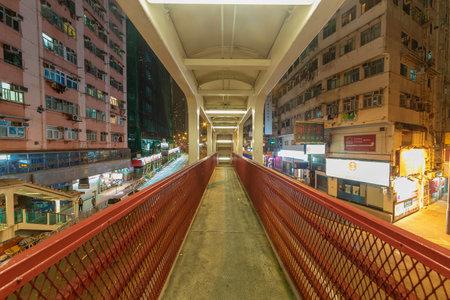 Hong Kong, China - February 27, 2019 : Empty narrow footbridge in midtown of Hong Kong city at night