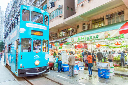 Hong Kong, China - February 15, 2019 : Double-decker tram passing through a busy street market in Hong Kong. Trams also a major tourist attraction and one of the most environmentally friendly ways of travelling in Hong Kong