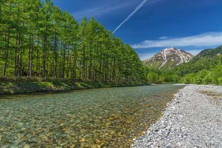 The pristine alpine water of Azusa River flowing in front of landscape view of Mount Hotaka-Dake on a sunny, blue sky day in Japanese Alps village of Kamikochi, Nagano, Japan. Фото со стока
