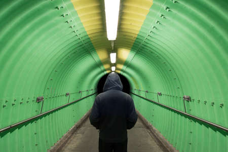 Silhouette of men standing at end of tunnel