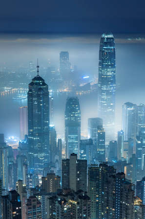 Misty night view of Victoria harbor in Hong Kong city Фото со стока