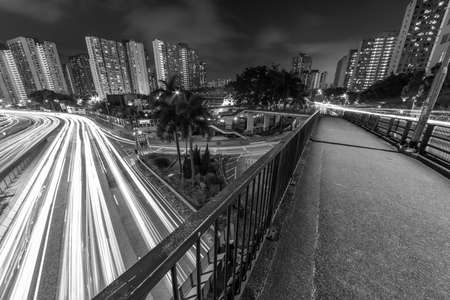Light trail of traffic on highway and pedestrian walkway in Hong Kong city at night