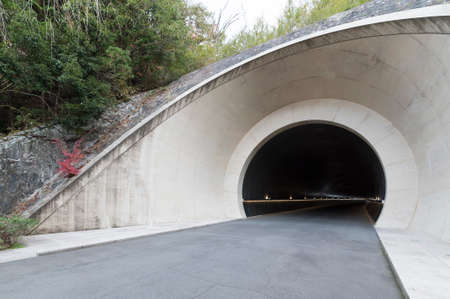 Entrance of futuristic tunnel. Heading through the mountain, on the road. 스톡 콘텐츠