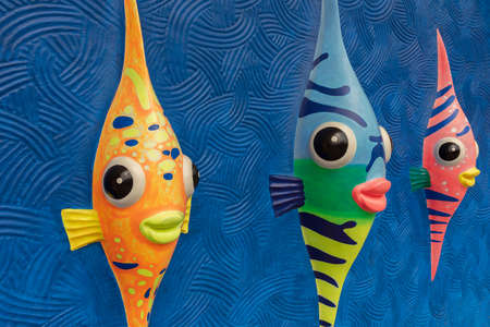 Funny cartoon colorful fish sculpture on wall