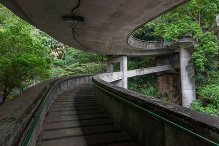 A old concrete curve walkway through the forest
