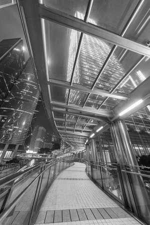 pedestrian walkway and skyscraper in Hong Kong city at night