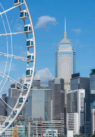 Ferris wheel and skyscraper in downtown district of Hong Kong city