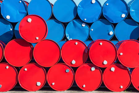 Colorful oil barrel stacked in row. Industrial background