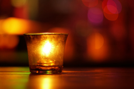 swimming candles: Candle in a glass in a warm tone. Abstract blur background with bokeh.