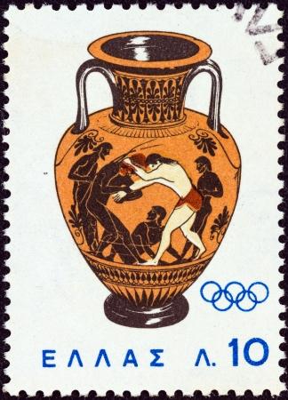 """deportes olimpicos: GRECIA - CIRCA 1964: Un sello impreso en Grecia de los """"Juegos Ol�mpicos de Tokio"""" Peleo tema muestra la lucha libre con Atlanta (�nfora) del a�o 500 aC, alrededor del a�o 1964. Editorial"""