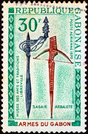 sello: GABON - CIRCA 1970: A stamp printed in Gabon from the Gabonaise weapons, folk art museum, Libreville issue shows assegai and crossbow, circa 1970. Editorial