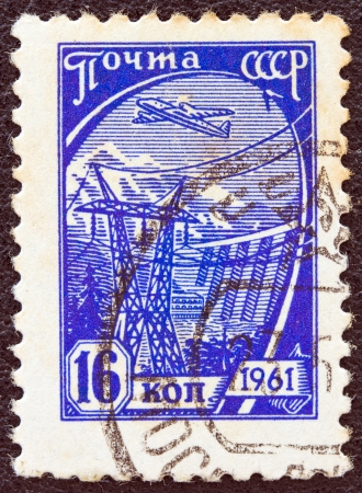 USSR - CIRCA 1961: A stamp printed in USSR from the tenth definitive issue shows an airliner over a Hydro-electric station, circa 1961.
