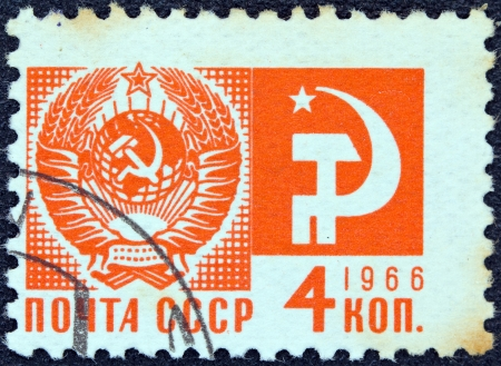 USSR - CIRCA 1966: A stamp printed in USSR from the 'Society and Technology' issue shows the Coat of Arms and communism emblem, circa 1966.