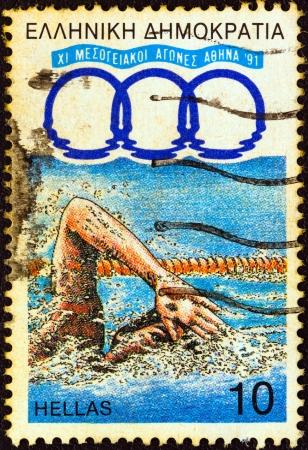 """piscina olimpica: GRECIA - CIRCA 1991: Un sello impreso en la Grecia de los """"Juegos del Mediterráneo del 11, Atenas"""" cuestión muestra a un nadador, alrededor del año 1991."""