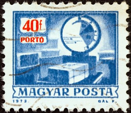 """Hungría - CIRCA 1973: Un sello impreso en Hungría de la """"Explotación Postal"""" cuestión muestra las escalas de paquetería, de auto-servicio de correos, alrededor de 1973."""