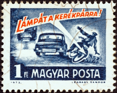 magyar: HUNGARY - CIRCA 1973: A stamp printed in Hungary from the Road Safety issue shows a car running down cyclist and Cyclist use a lamp ! inscription, circa 1973.