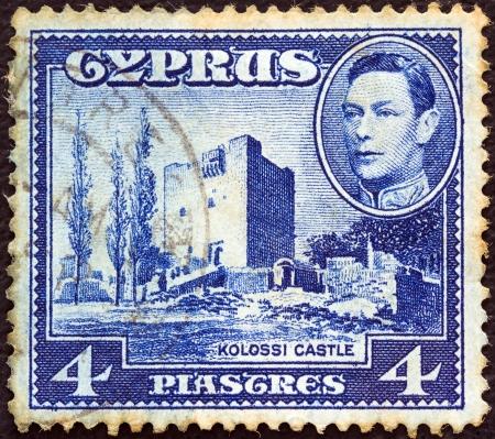 kibris: CYPRUS - CIRCA 1938: A stamp printed in Cyprus shows Kolossi Castle and King George VI, circa 1938.