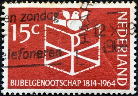 timbre: NETHERLANDS - CIRCA 1964: A stamp printed in the Netherlands issued for the 150th anniversary of Netherlands Bible Society shows Bible and Dove, circa 1964.  Editorial