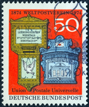 GERMANY - CIRCA 1974: A stamp printed in Germany issued for the Centenary of Universal Postal Union (UPU) shows antique mailboxes, circa 1974.  Stock Photo - 16089176