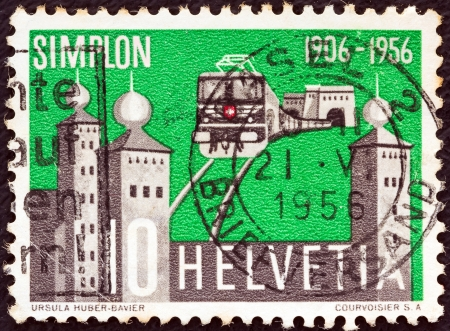 SWITZERLAND - CIRCA 1956: A stamp printed in Switzerland issued for the 50th anniversary of opening of Simplon Tunnel shows electric train emerging from the tunnel and Stockalper Palace, circa 1956.  Stock Photo - 16089187