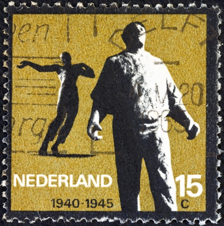 timbre: NETHERLANDS - CIRCA 1965: A stamp printed in the Netherlands from the Resistance Commemoration issue shows Docker (Amsterdam) and Killed in Action (Waalwijk), circa 1965.