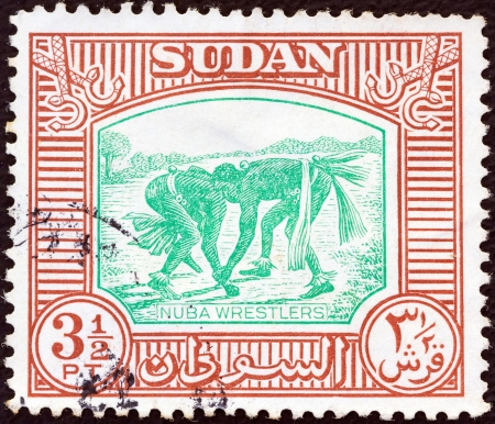 wrestlers: SUDAN - CIRCA 1951: A stamp printed in Sudan shows Nuba wrestlers, circa 1951.