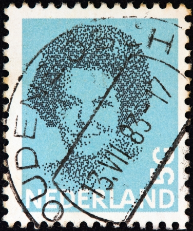 beatrix: NETHERLANDS - CIRCA 1981: A stamp printed in the Netherlands shows a portrait of Queen Beatrix, circa 1981.  Editorial