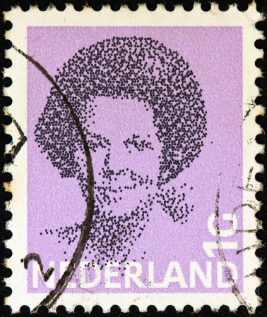 regnant: NETHERLANDS - CIRCA 1981: A stamp printed in the Netherlands shows a portrait of Queen Beatrix, circa 1981.  Editorial