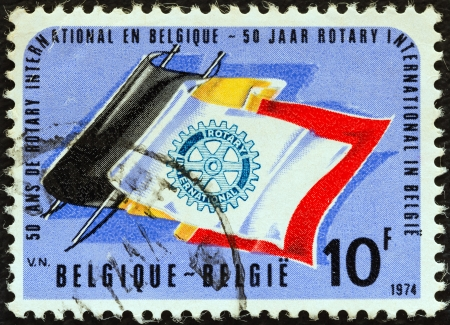 stempeln: BELGIUM - CIRCA 1974: A stamp printed in Belgium issued for the 50th anniversary of Rotary International in Belgium shows Rotary Emblem on Belgian Flag, circa 1974.  Editorial