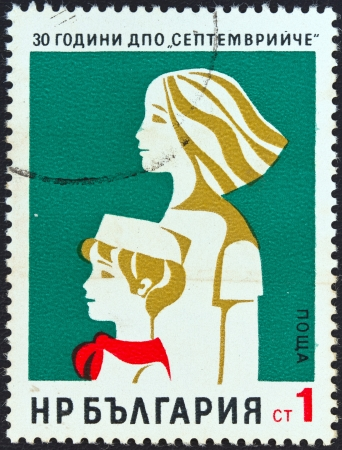 bulgaria girl: BULGARIA - CIRCA 1974: A stamp printed in Bulgaria issued for the 30th anniversary of Dimitrovs Septembrist Pioneers Organization shows young pioneer and Komsomol girl, circa 1974.