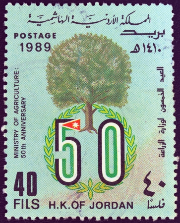 the hashemite kingdom of jordan: JORDAN - CIRCA 1989: A stamp printed in Jordan issued for the 50th anniversary of the Ministry of Agriculture shows a tree and emblem, circa 1989.