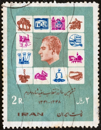 IRAN - CIRCA 1970: A stamp printed in Iran from the Declaration of the Shahs Reform Plan issue shows symbols of reform laws and Shah Mohammad Reza Pahlavi, circa 1970.
