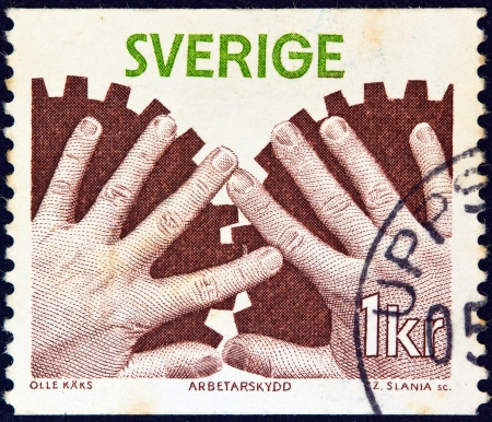stempeln: SWEDEN - CIRCA 1976: A stamp printed in Sweden from the Industrial Safety issue shows hands and cogwheels, circa 1976.