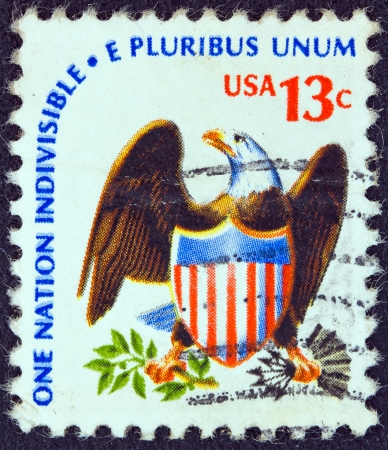 e pluribus unum: USA - CIRCA 1975: A stamp printed in USA from the Americana issue shows an eagle and shield and the inscription One Nation Indivisible-E Pluribus Unum, circa 1975.