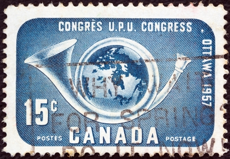 posthorn: CANADA - CIRCA 1957: A stamp printed in Canada issued for the 14th UPU Congress, Ottawa shows Globe within posthorn, circa 1957.